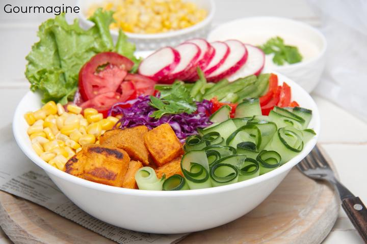 A white bowl filled with sweet potatoes, various vegetables and salads