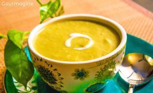 Eine verzierte Schüssel gefüllt mit Brokkoli-Crème-Suppe auf einem blaugrünen Teller