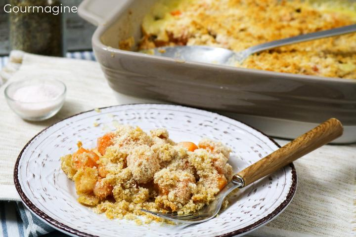 Carrots gratinated with cheese on a decorated plate next to a casserole dish with a carrots casserole
