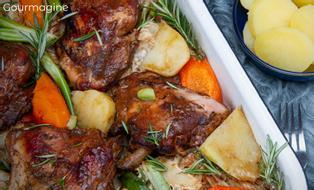 Baked chicken pieces, potatoes, carrots and rosemary served on a bed of cabbage in an oven dish