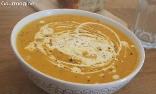 A white bowl filled with brown sweet potato and carrot soup and a drizzle of crème fraîche