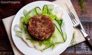 Ein weisser Teller mit einem Gurkensalat-Bett, auf welchem Hambuger angerichtet sind
