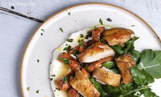 Chicken pieces, carrots and rocket on a bed of yoghurt on a white plate