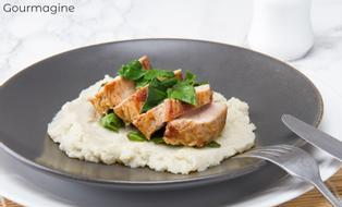 Several pieces of pork on a cauliflower puree served on a black plate
