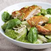 A white bowl with noodles, chicken and cucumber