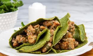 Two green spinach crêpes filled with a chicken mixture served on a white plate