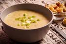 A dark brown bowl filled with potato leek soup