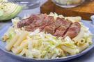 A sliced, fried steak served on a plate with macaroni and cabbage