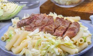 Ein geschnittenes, gebratenes Steak angerichtet auf einem Teller mit Makkaroni und Kabis