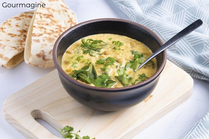A tomato yoghurt lentil curry served in a black bowl next to two pita breads