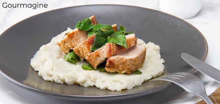 Bild eines Tellers mit geschnittenem Schweinefleisch und feinem Blumenkohlpüree