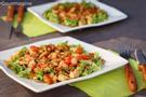 Zwei viereckige Teller mit gebratenem Poulet, Peperonistücken und grünen Salatblättern