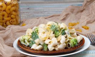 Ein brauner Teller gefüllt mit Hörnli, Brokkoli und Pilzen mit Käse drübergestreut
