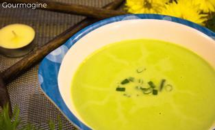 A cauliflower spinach soup served in a white and blue bowl