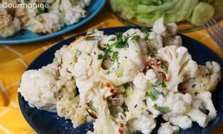 Blumenkohlstücke mit Käse, Bundzwiebeln und Peterli überbacken auf einem blauen Teller angerichtet