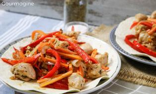A tortilla filled with chicken pieces, peppers and carrots on a plate