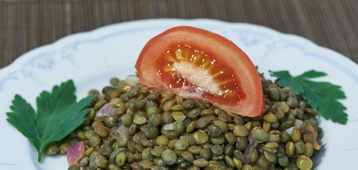 A white plate with lentils and a tomato slice