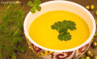 A decorated bowl filled with yellow carrot soup