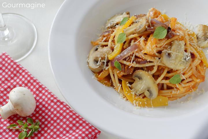 Spaghetti, Pilze, Zwiebeln und Tomatensauce angerichtet auf einem weissen Teller