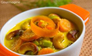 An orange and white bowl filled with carrots, leeks, parsnips and cashews in a curry sauce