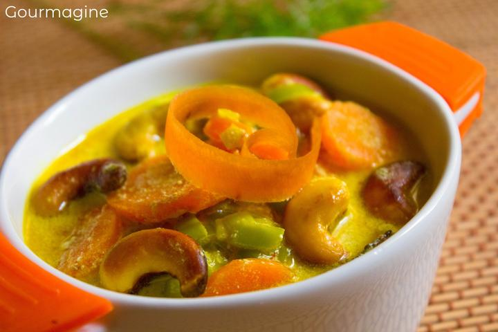 Eine orange-weisse Schüssel gefüllt mit Rüebli, Lauch, Pastinaken und Cashewnüssen in einer Currysauce