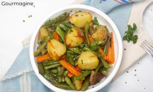 A white bowl with roasted green beans, potatoes, carrots and onions