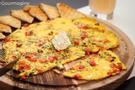 Eine Omelette mit Peperoni, Zucchetti und Feta angerichtet auf einem hölzernen Teller