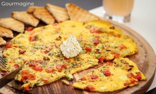 An omelette with pepperoni, courgettes and feta on a wooden plate