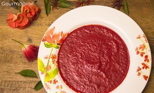 Ein verzierter weisser Teller gefüllt mit Curry-Randen-Suppe und dekorativen Rosenblättern