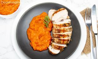 A roasted chicken breast cut into several pieces served with carrot puree on a black plate