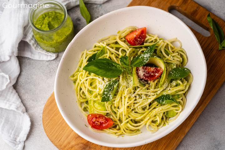 A white bowl filled with spaghetti with pesto and tomatoes