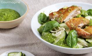 A white bowl with noodles, chicken and cucumber next to a bowl with green sauce and a plate of cut cucumbers