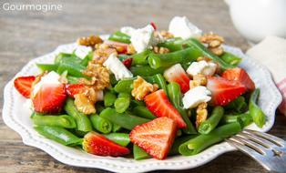 Grüne Bohnen mit Baumnüssen, Feta und Erdbeeren angerichtet auf einem weissen Teller