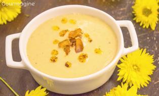 Eine Blumenkohl-Kichererbsen-Suppe in einem weissen Topf angerichtet und mit gelben Blumen dekoriert