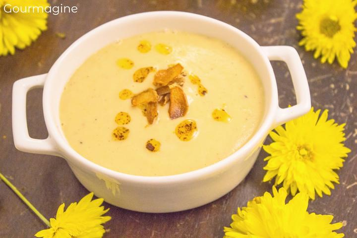 A cauliflower chickpea soup served in a white pot and decorated with yellow flowers