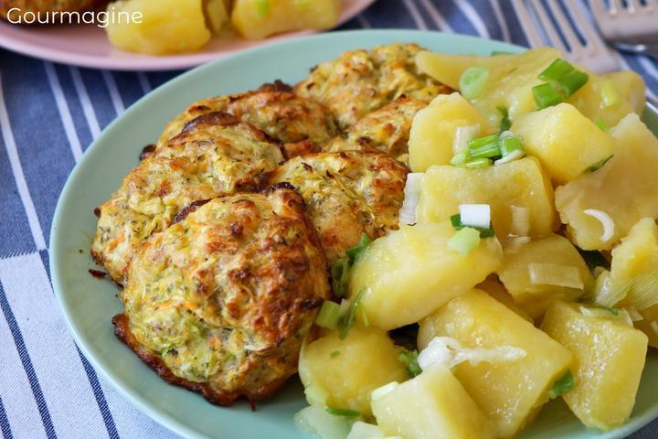 Mehrere Zucchetti-Bällchen und Kartoffelstücke angerichtet auf einem grünen Teller