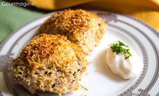 Zwei Pouletstücke mit einer Käse-Basilikum-Kruste angerichtet auf einem weissen Teller