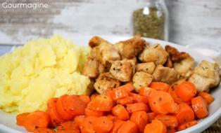 Steamed carrots, fried chicken pieces and mashed potatoes served on a white plate