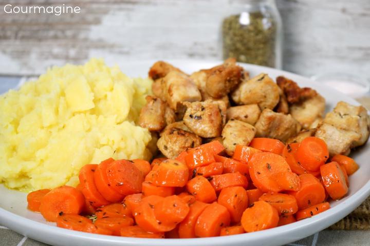 Gedämpfte Rüebli, gebratene Pouletstücke und Kartoffelstock angerichtet auf einem weissen Teller