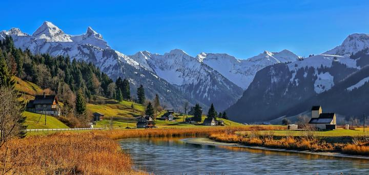 Image of a green nature landscape with a small lake and snow-covered mountains