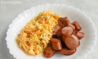 Kabis-Rüebli-Salat und ein geschnittenes Wienerli angerichtet auf einem weissen Teller