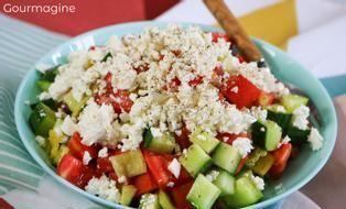 A green bowl filled with cucumbers, tomatoes, pepperoni and cheese