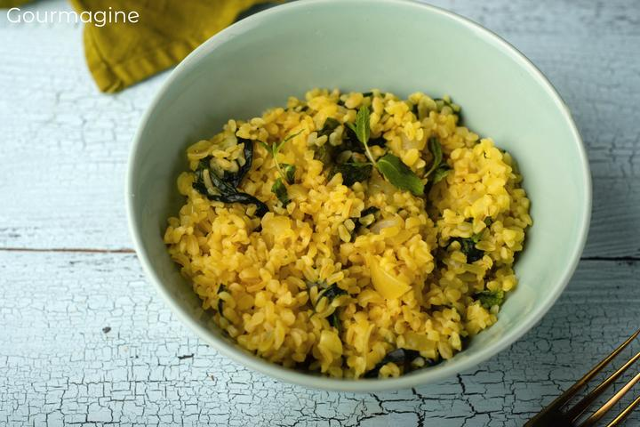 Cooked bulgur and spinach served in a grey-blue bowl