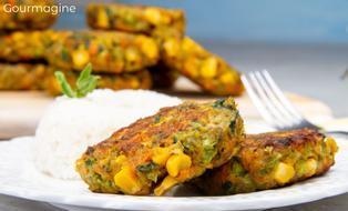 Zwei braune Gemüse-Plätzchen aus Brokkoli, Mais und Spinat angerichtet auf einem weissen Teller zusammen mit weissem Reis