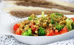 A white bowl filled with a salad of broccoli, tomatoes and walnuts