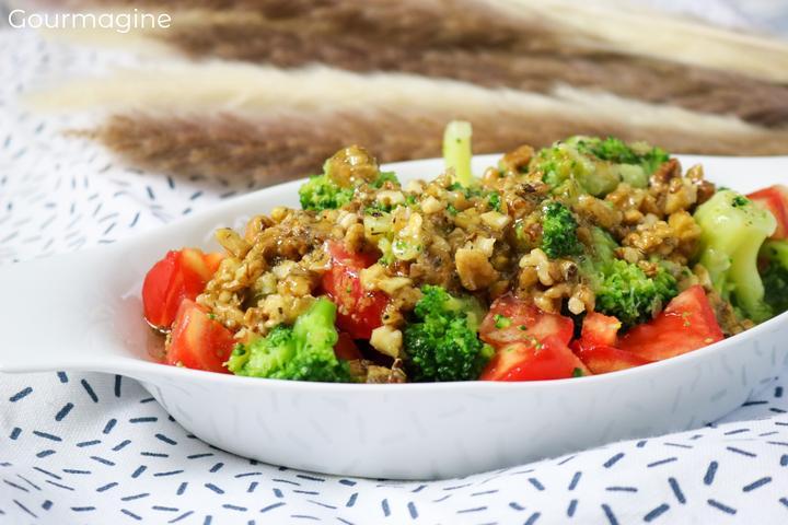 Eine weisse Schüssel gefüllt mit Salat aus Brokkoli, Tomaten und Walnüssen