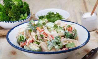 A white bowl filled with farfalle, broccoli, peppers and courgettes covered with a salad dressing