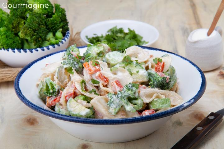 Eine weisse Schüssel gefüllt mit Farfalle, Brokkoli, Peperoni und Zucchetti bedeckt mit einer Salatsauce