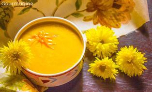 A bowl filled with lentil soup next to yellow flowers