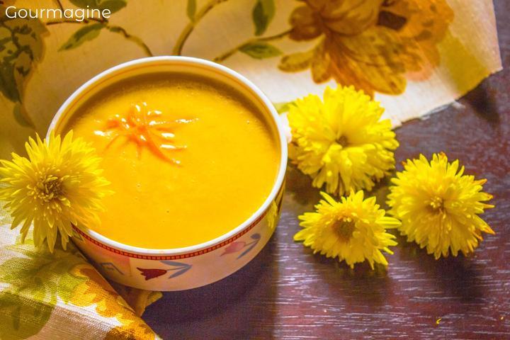 Eine Schüssel gefüllt mit Linsen-Suppe neben gelben Blumen